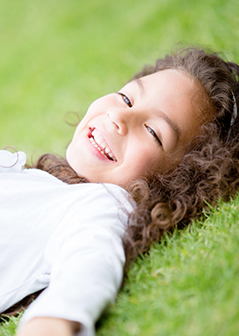 beautiful child laying on the ground smiling